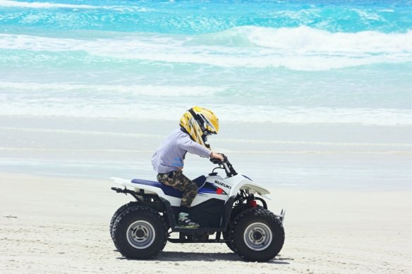 my little guy on the quad bike: confident, focused, wind in his shirt